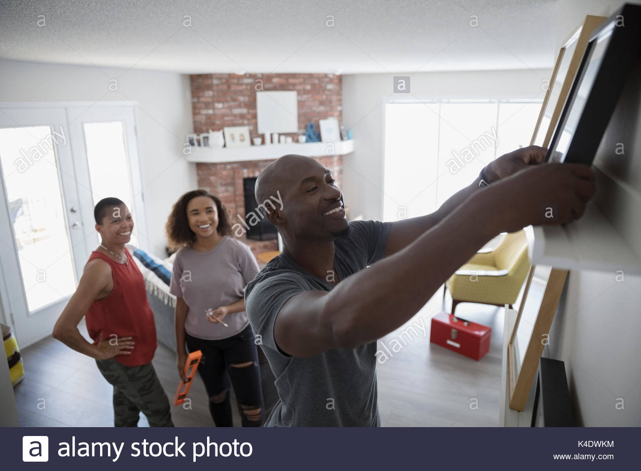 Family hanging picture frames on shelf in living room - Stock Image