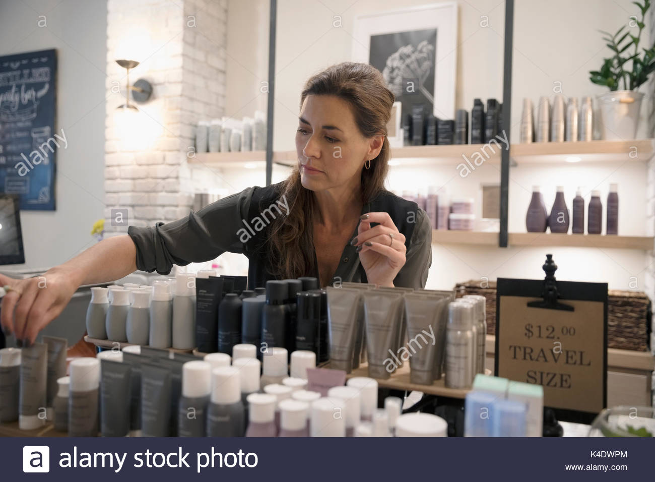 Female salon shop owner arranging beauty product display - Stock Image