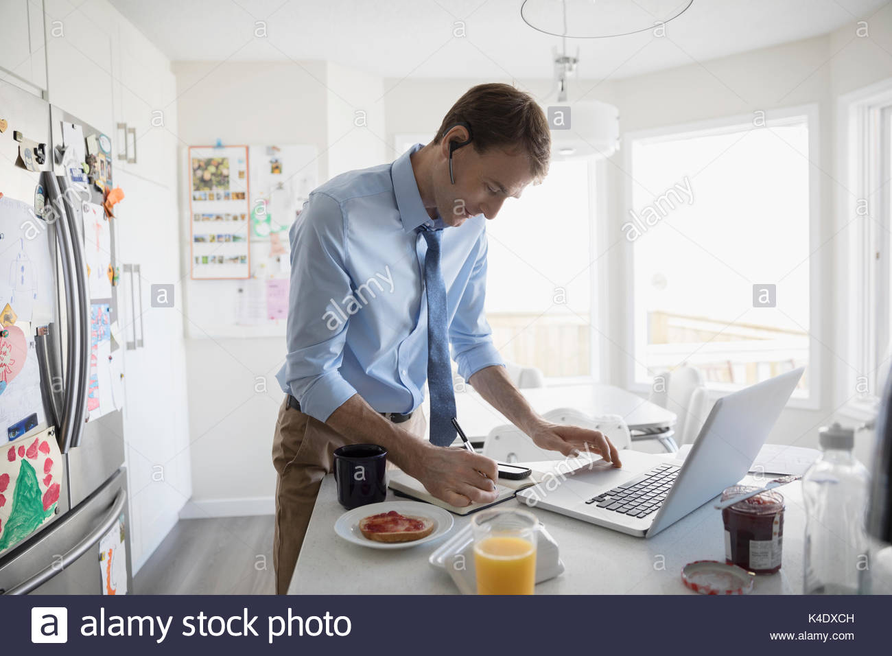 Businessman eating breakfast and working at laptop in morning kitchen - Stock Image