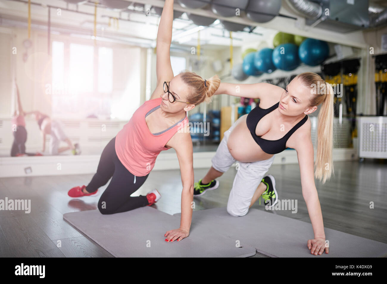 Side portrait of pregnant woman exercising with personal trainer Stock Photo