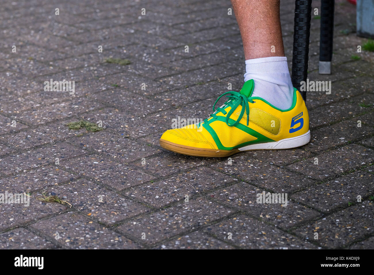A left foot wearing a brightly coloured yellow Umbro trainer. - Stock Image