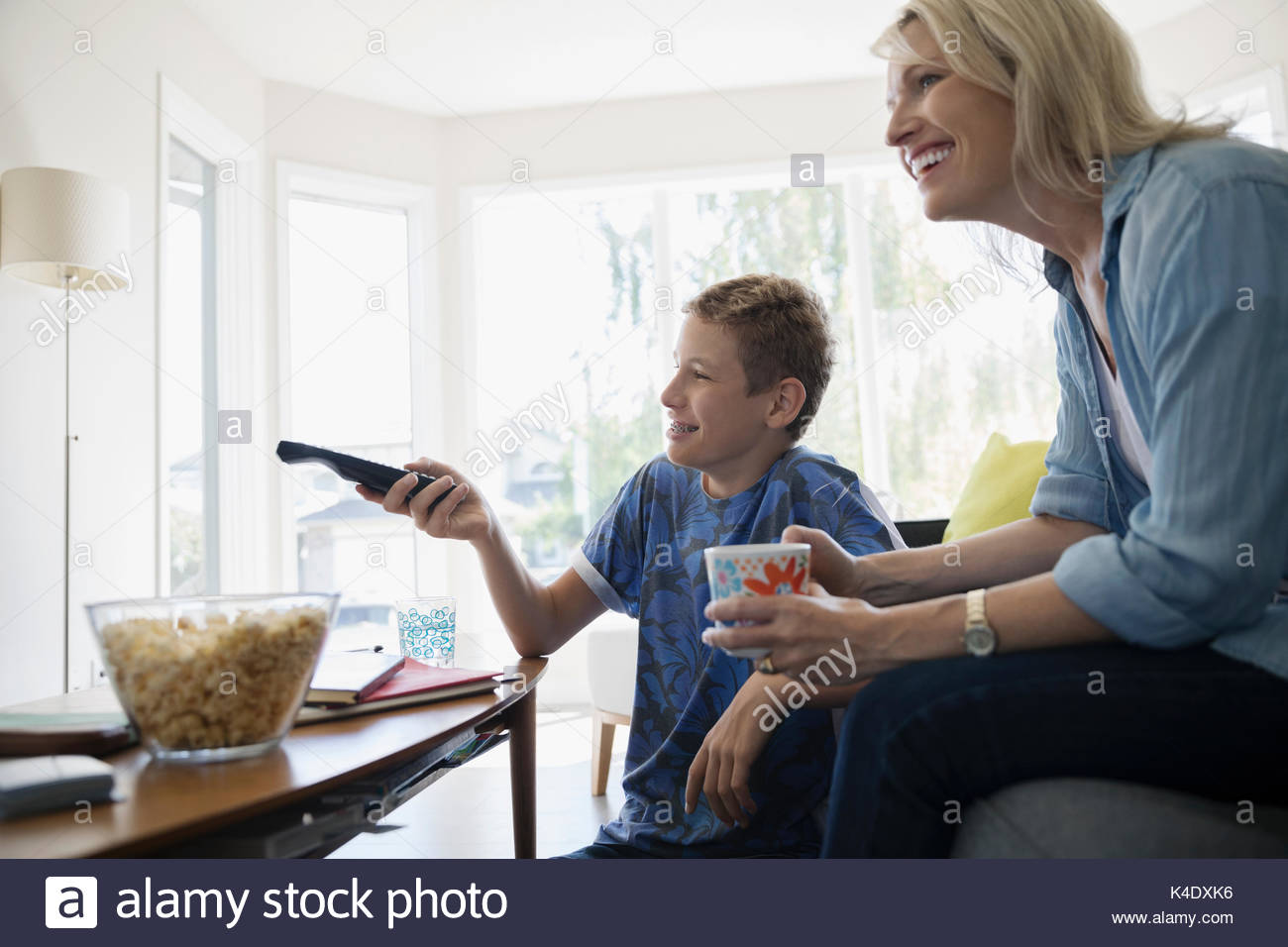 Mother and pre-adolescent son watching TV and eating popcorn in living room - Stock Image