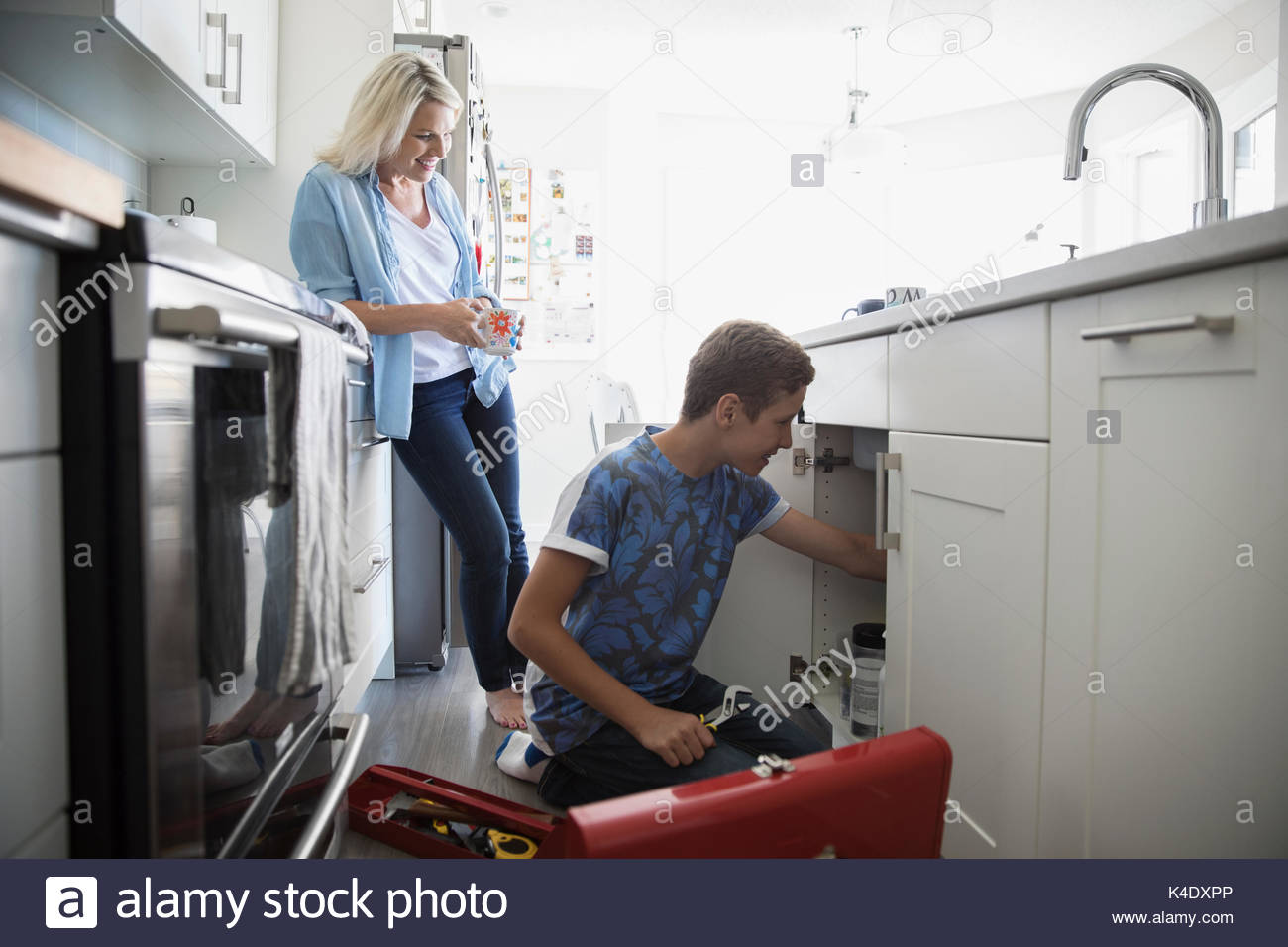 Single mother watching pre-adolescent son fixing plumbing under kitchen sink - Stock Image