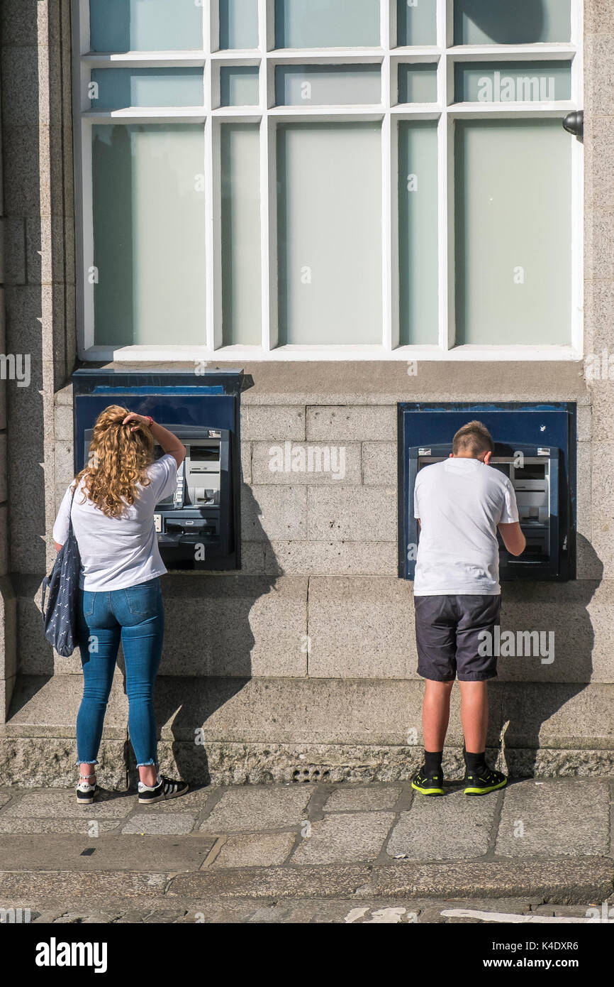 ATM - people using ATM in a city centre. - Stock Image