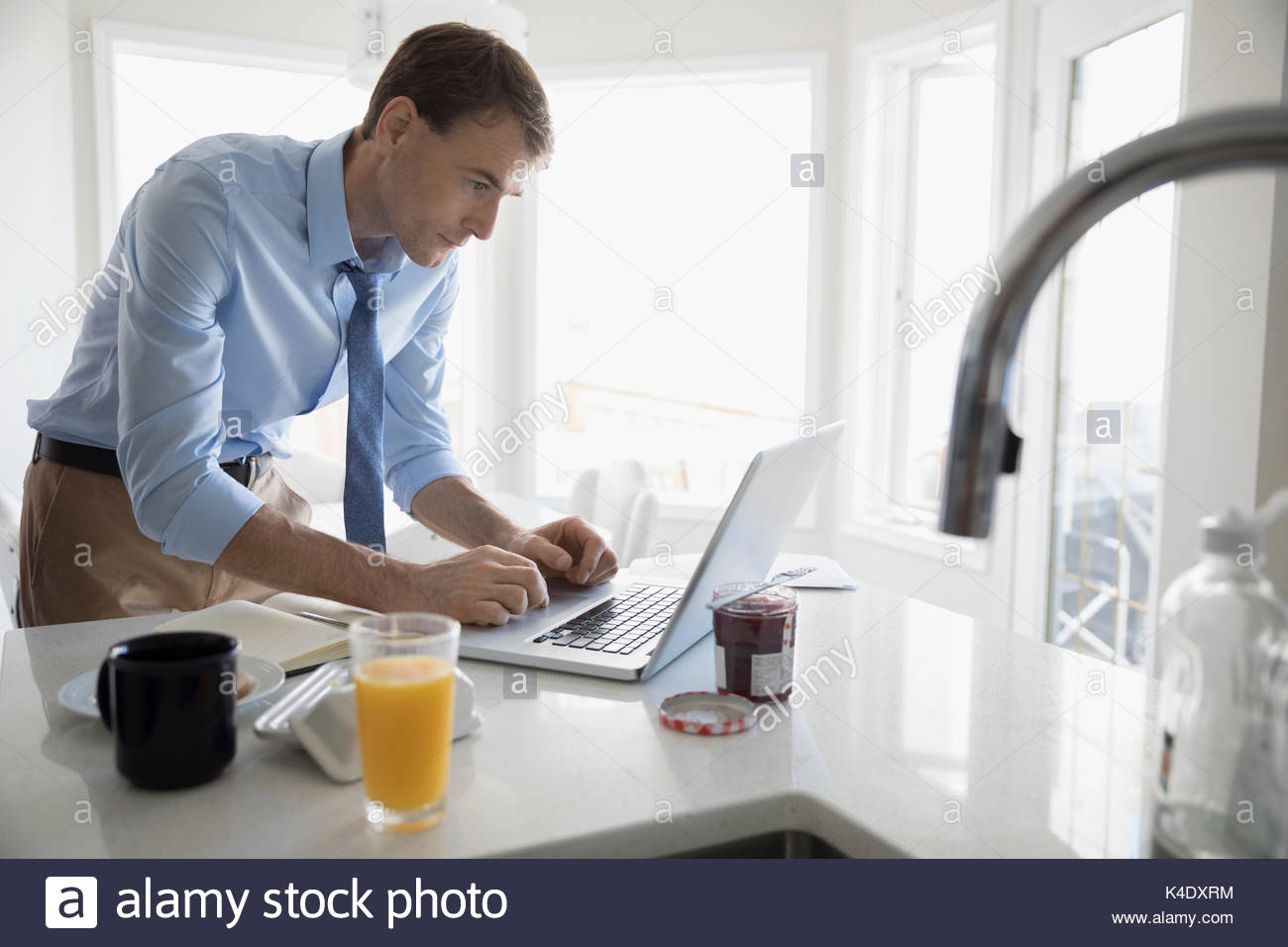Businessman working at laptop in morning breakfast kitchen - Stock Image