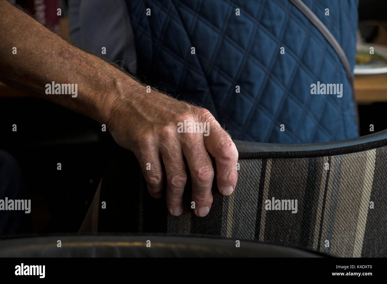 Age - the hand of an elderly person holding the back of a chair. - Stock Image
