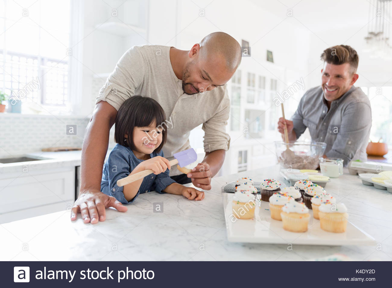 Male gay parents and adopted toddler daughter baking cupcakes in kitchen - Stock Image