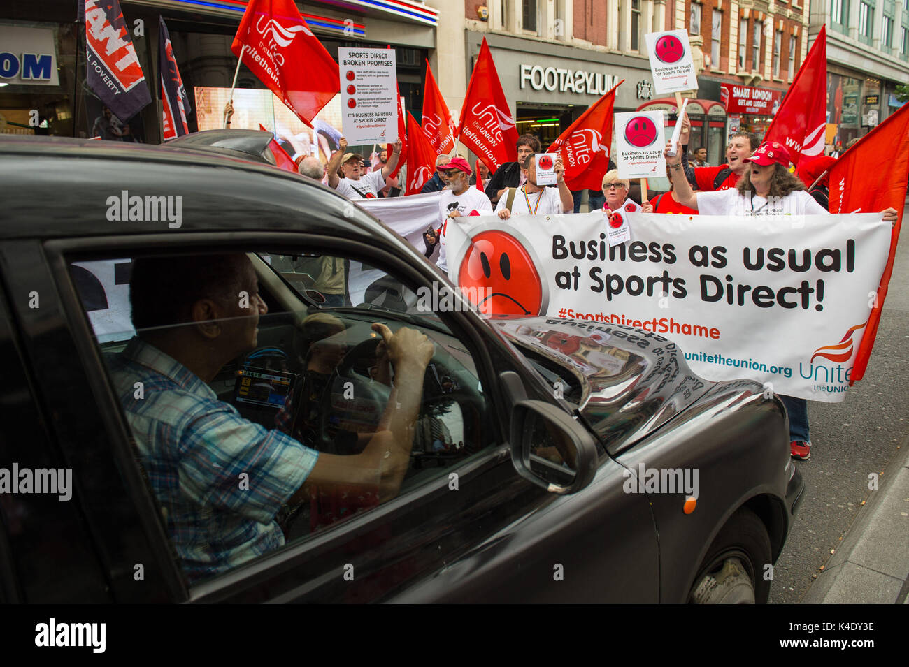 Unite the union protesters outside the Sports Direct flagship store on Oxford Street in London as the troubled retailer has been accused of reneging on a promise to offer guaranteed hours to staff on zero hour contracts in a fresh blow to the company ahead of its annual meeting. - Stock Image