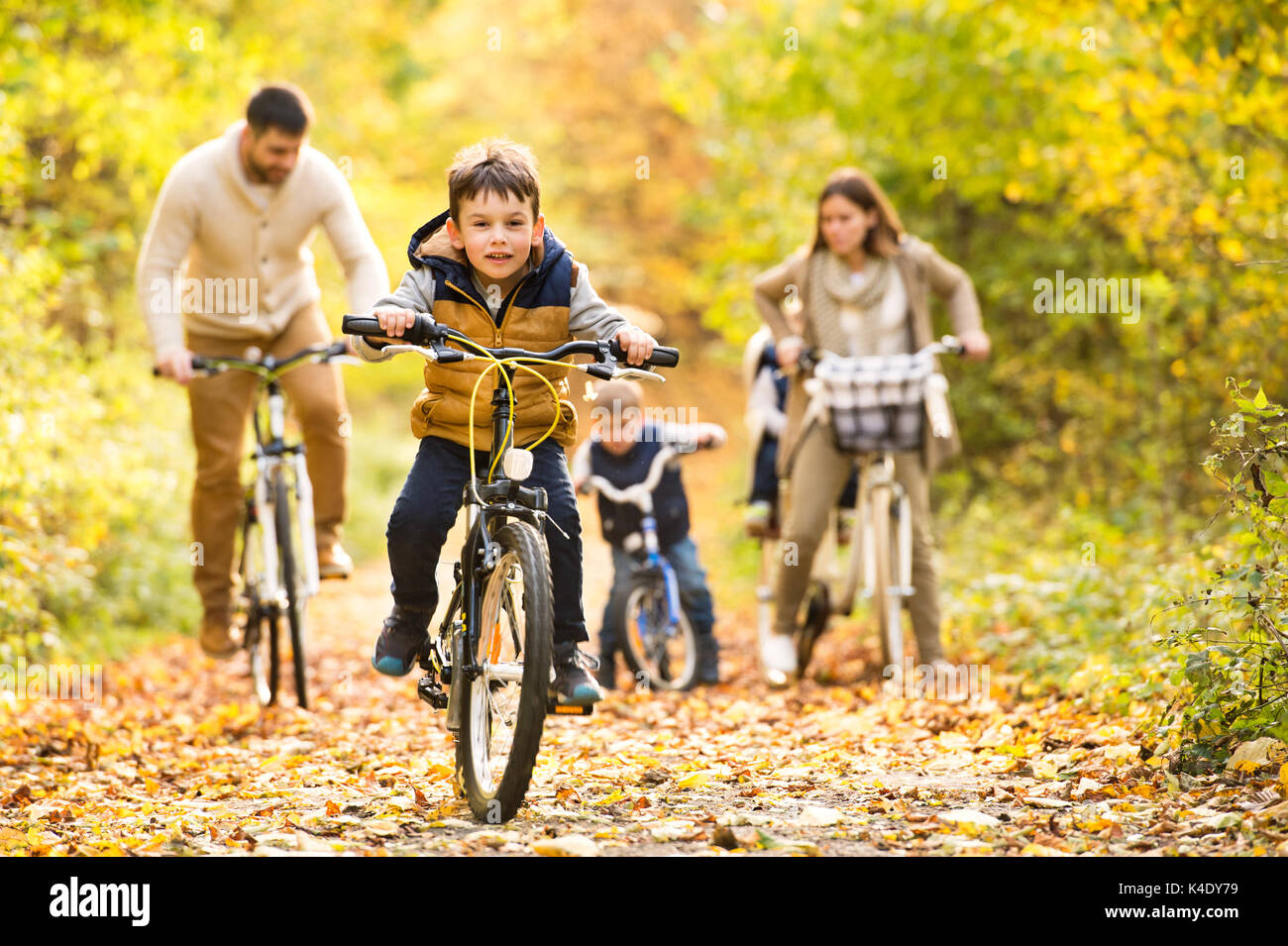 Young family in warm clothes cycling in autumn park Stock Photo