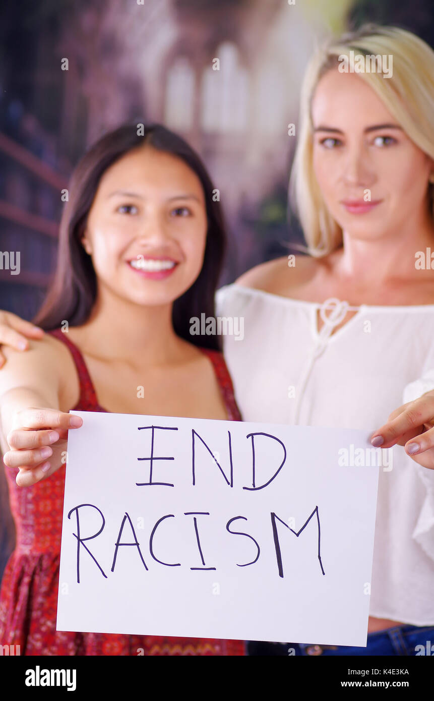 Two young women blonde and latin girl smiling and breaking racism idiosyncrasy from a american person and foreign people, holding a piece of paper that is written end racism. Racism, violence or discrimination concept - Stock Image