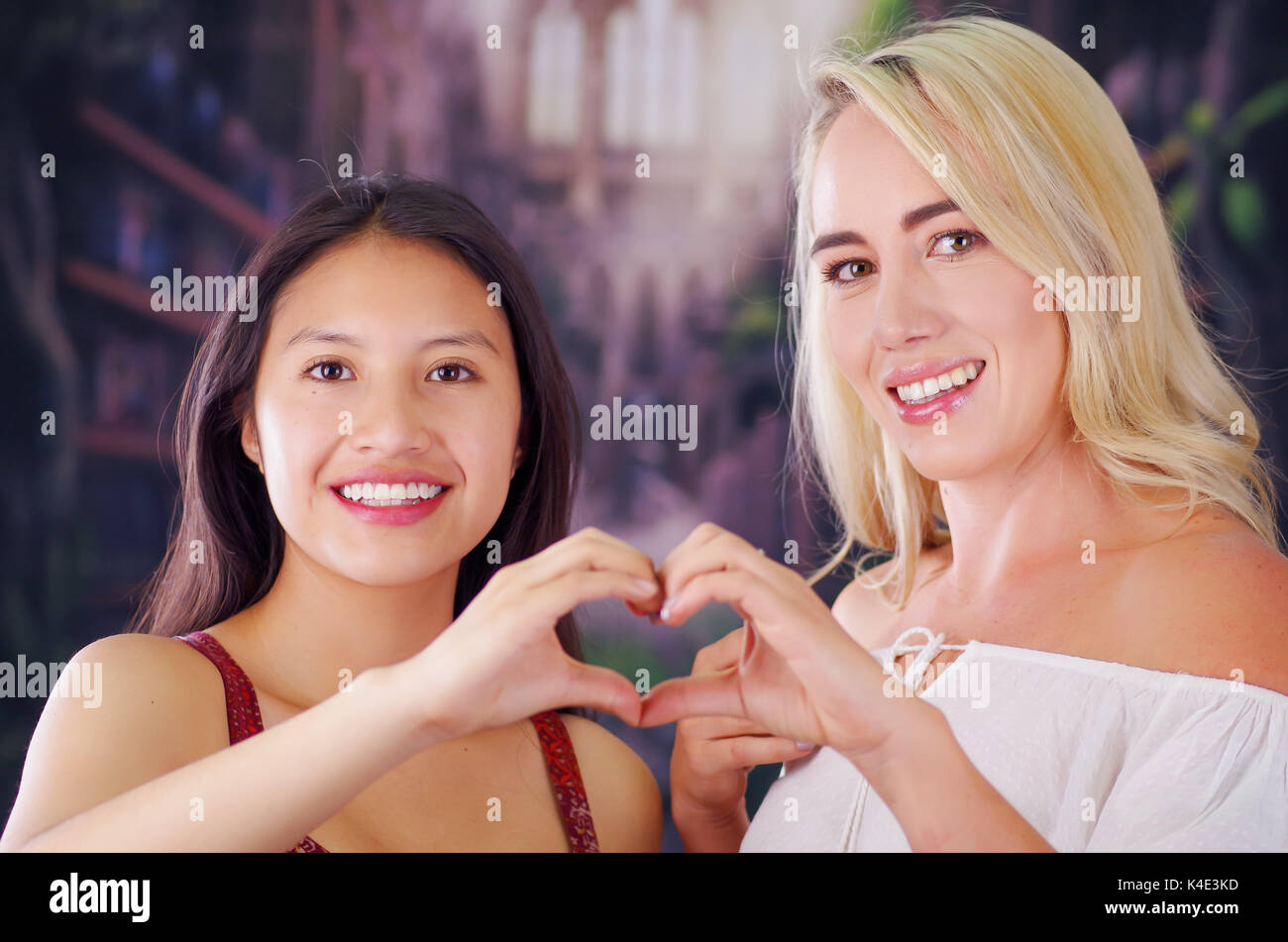 Two young women blonde and latin girl smiling and breaking racism idiosyncrasy from a american person and foreign people, both doing a heart sign with teir hands, racism, violence or discrimination concept - Stock Image