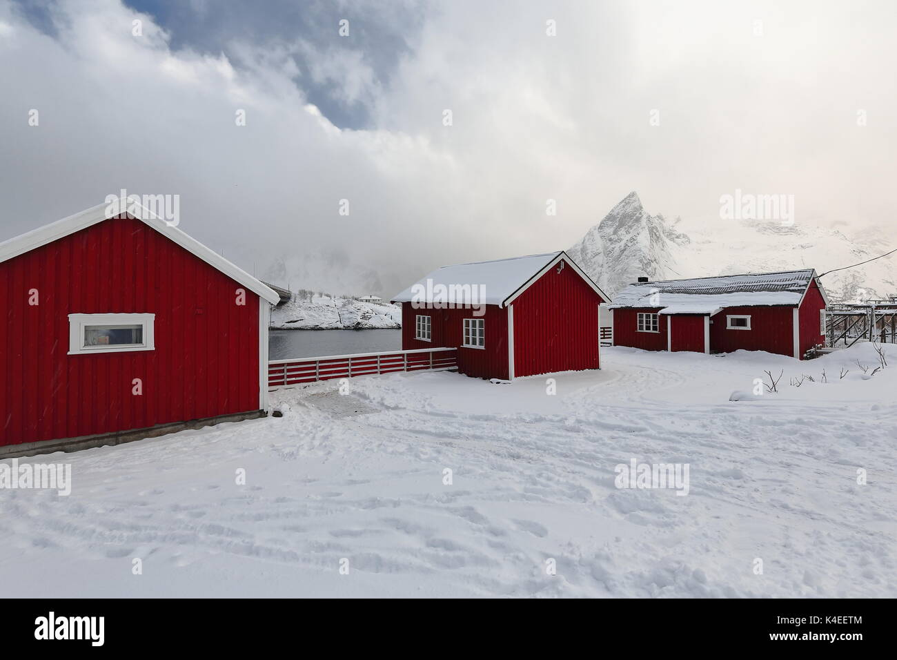 Red wooden rorbuer under heavy snowfall-traditional seasonal fishing huts-now for tourist use. Snowcapped Olstinden-Rostadtinden mts.across Reinefjord - Stock Image