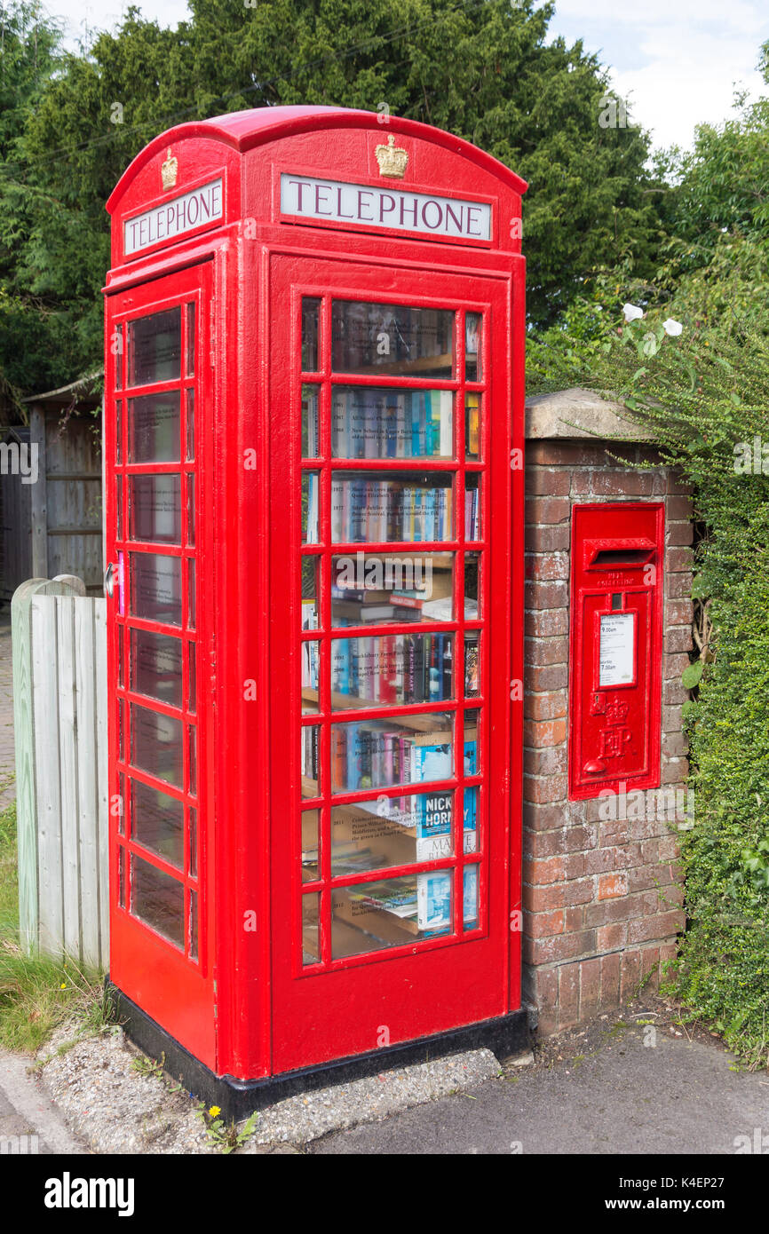 Red telephone kiosk (book exchange) and post box, Chapel Row Stores, Chapel Row, Bucklebury, Berkshire, England, United Kingdom - Stock Image
