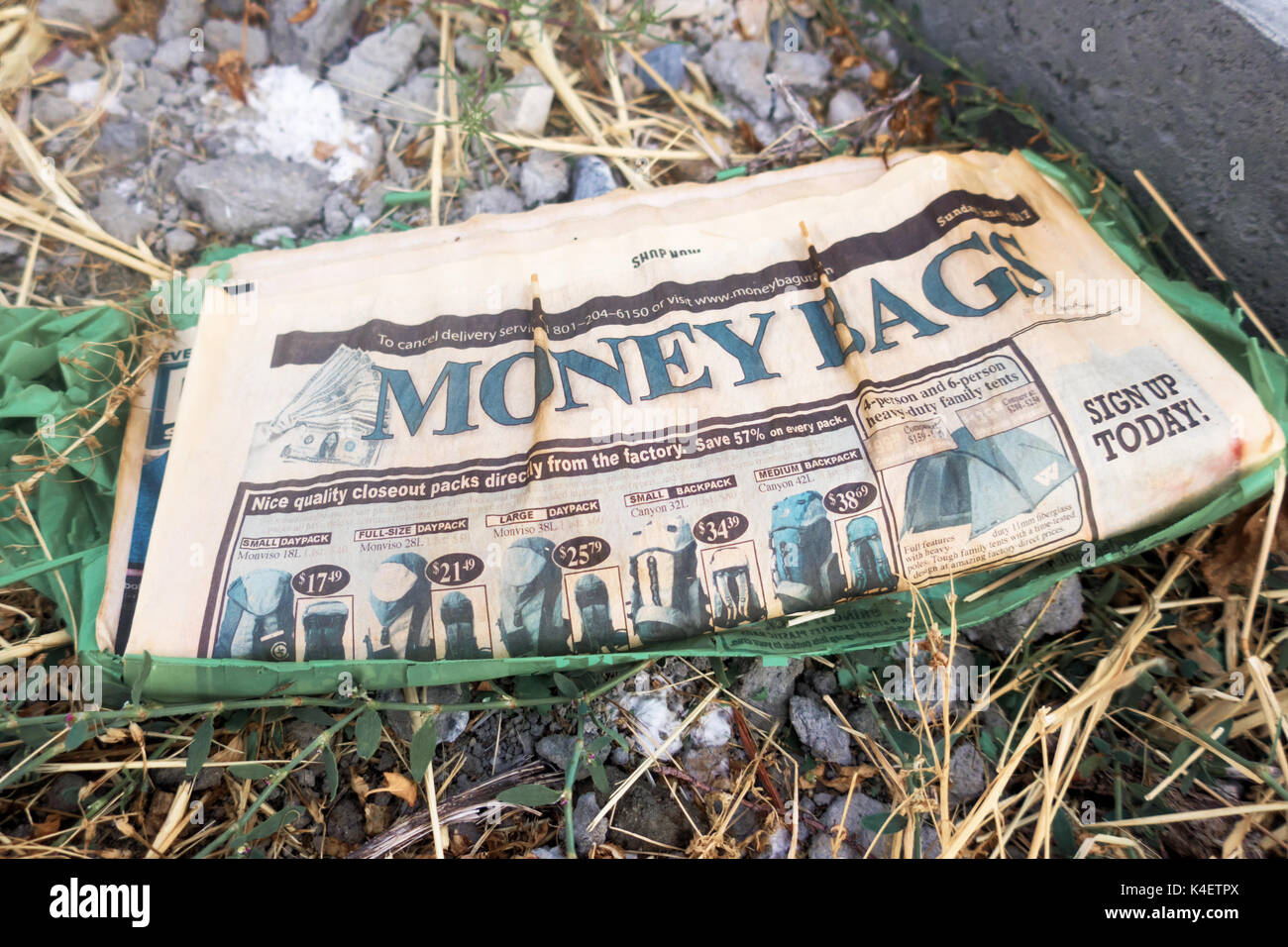 A wet, yellow advertisers newspaper lying neglected on the ground. - Stock Image