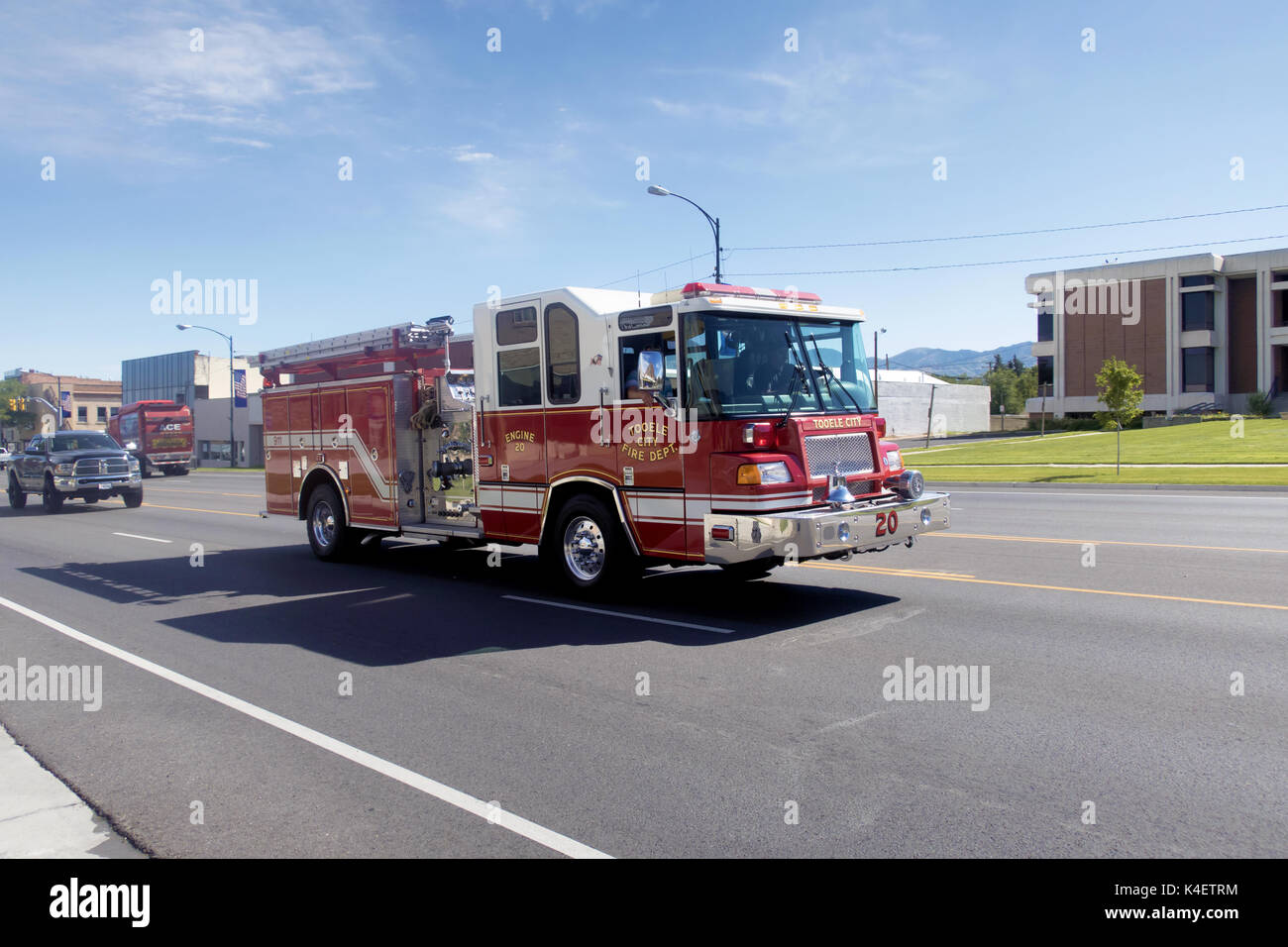 A red fire truck driving down main street after a canceled call. - Stock Image