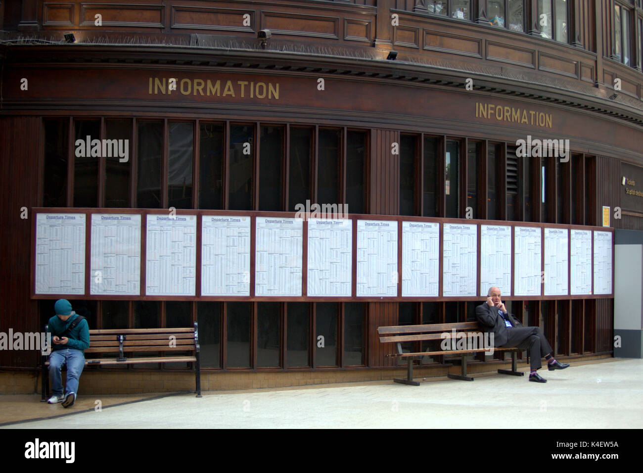 wooden paneled information railway train tables  on side concourse central station Glasgow - Stock Image