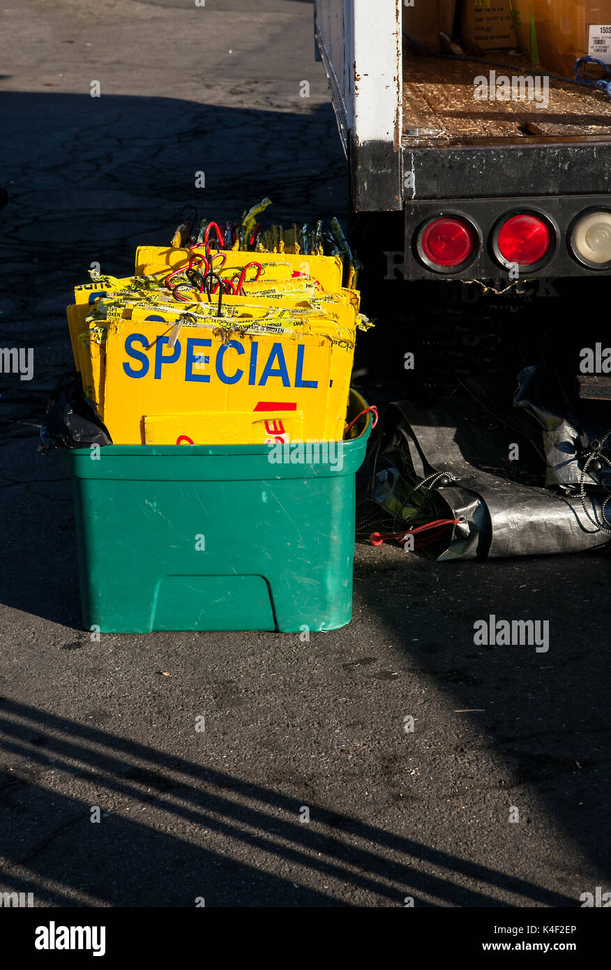 Vendor is unloading his truck hoping for a successful day at the swap meet.  He has a bucket of bright yellow signs ready to attract some customers - Stock Image