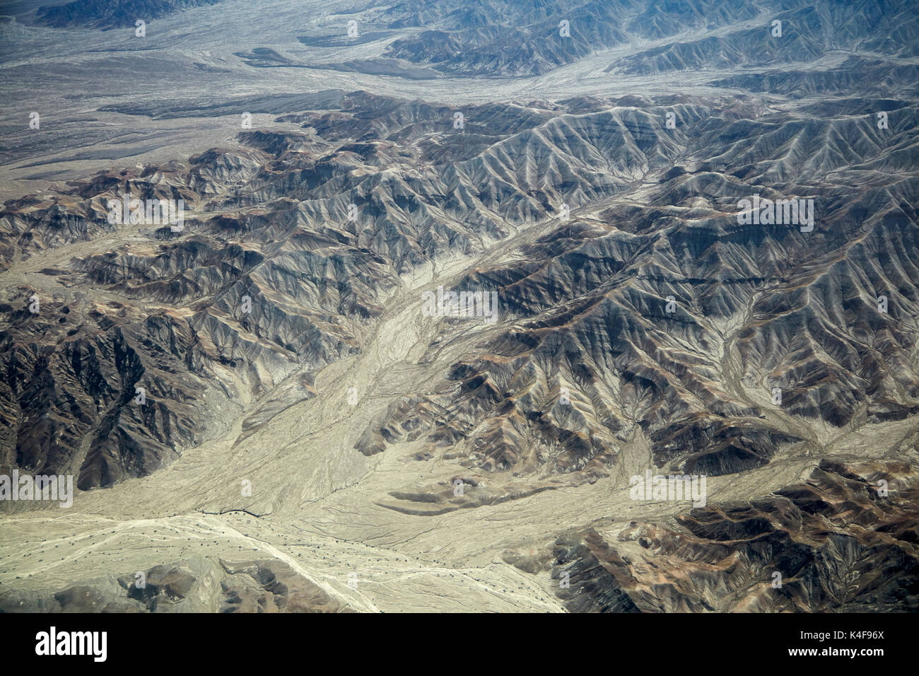 Eroded hills and dry river beds in the desert south of Ica, Peru, South America - aerial - Stock Image