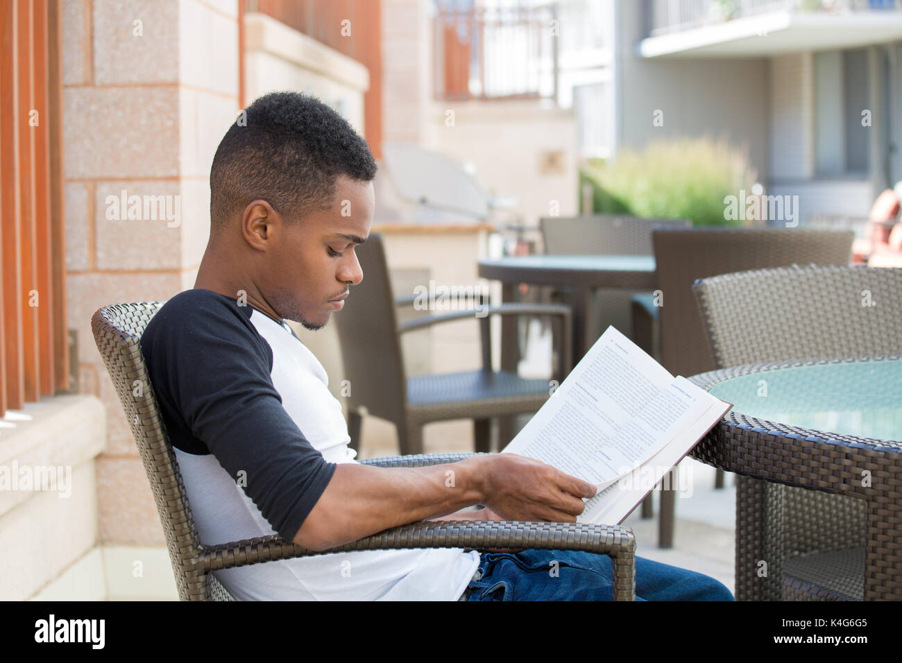 Closeup portrait, smart young man with intense concentration, sitting down and reading book, isolated outdoors background.  knowledge is power concept - Stock Image