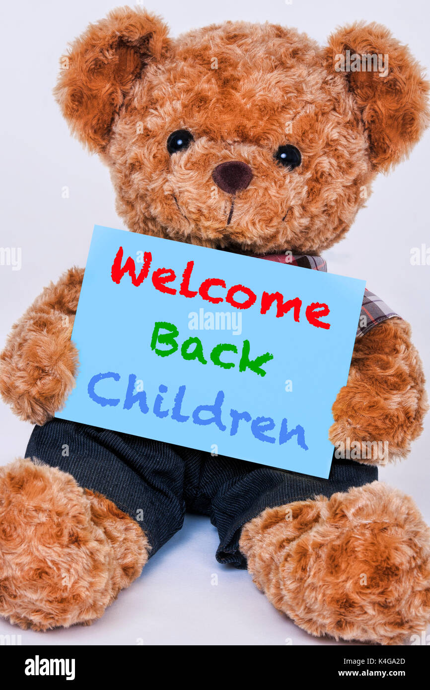Cute teddy bear holding a blue sign hte says Welcome back Children isolated on a white background - Stock Image