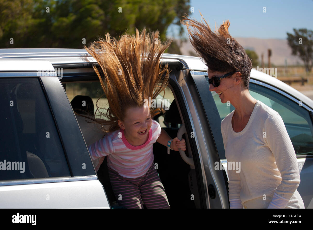 A mother and daughter experience high winds next to their vehicle in central California - Stock Image