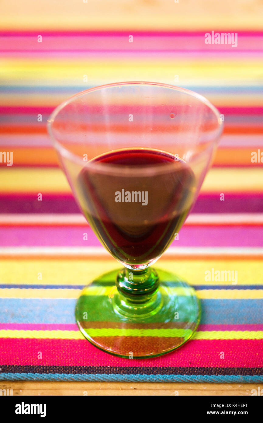 A glass of red wine on colourful striped table cloth - Stock Image