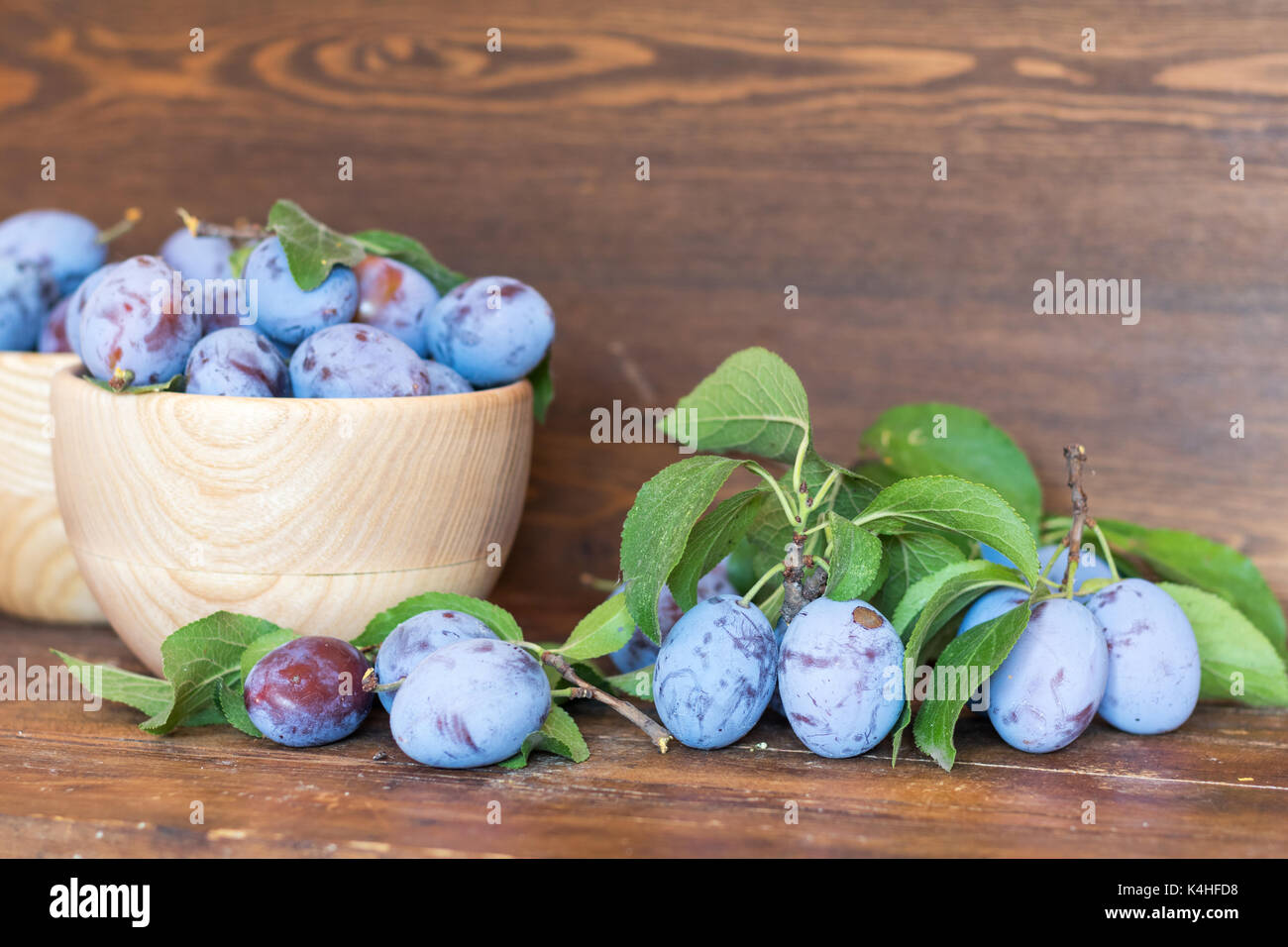 Fresh plums with green leaves in wooden pot on the dark wooden table. Shallow depth of field. Toned. - Stock Image