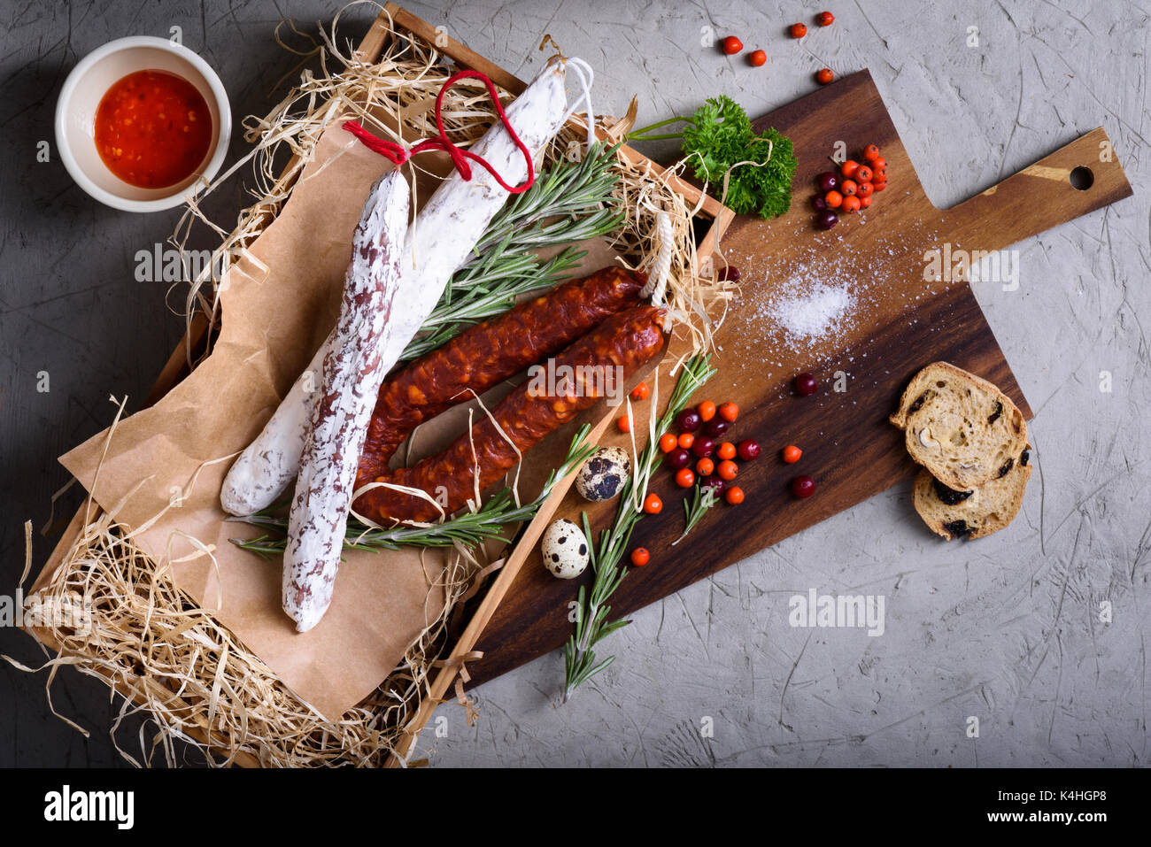 Salami smoked sausages antipasto ingredients. Meat products in a box with autumn berries and herbs. Top view, copy - Stock Image