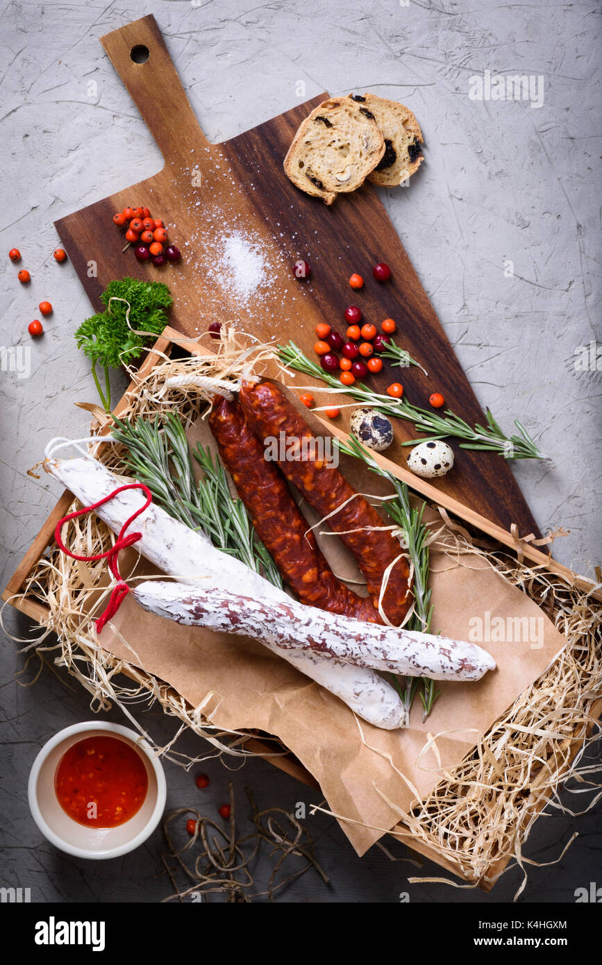 Antipasto traditional spanish meat snack with bread, herbs, autumn berries. Above view. - Stock Image