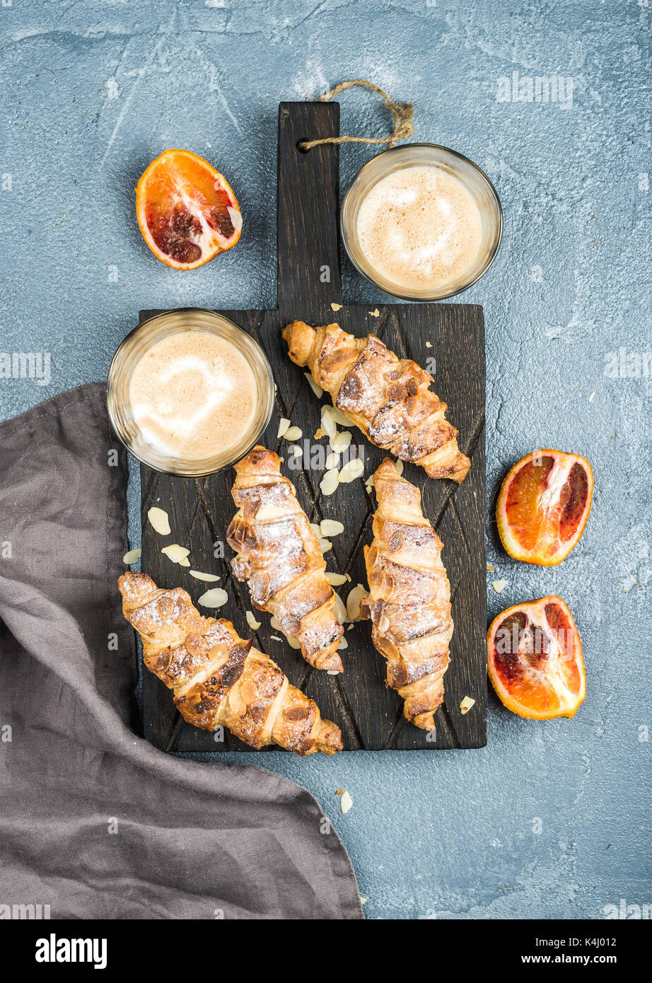 Traditional Italian style home breakfast. Latte in glasses, almond croissants and red bloody Sicilian oranges over concrete textured table - Stock Image
