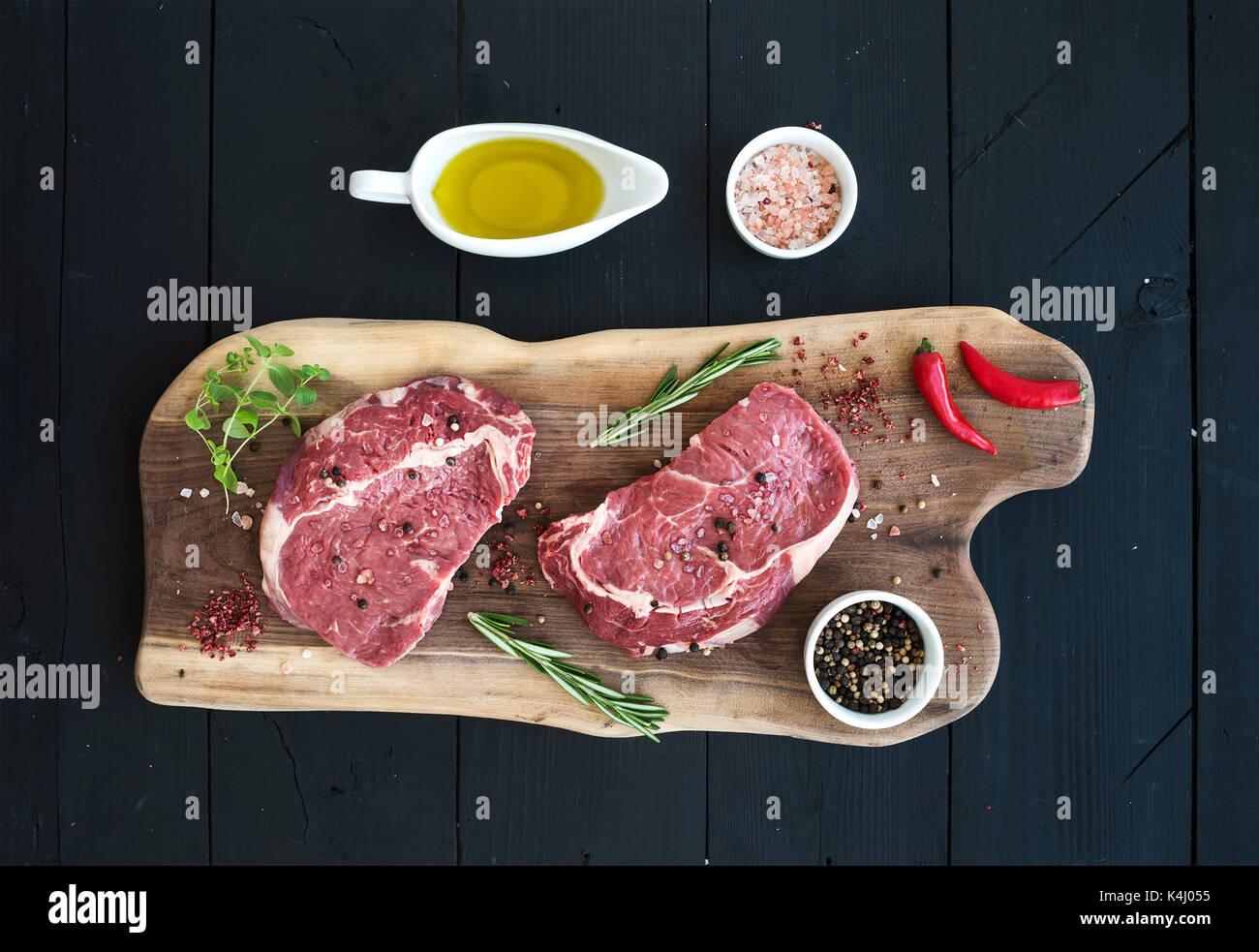 Raw fresh meat Ribeye steak entrecote and seasonings on cutting board Stock Photo