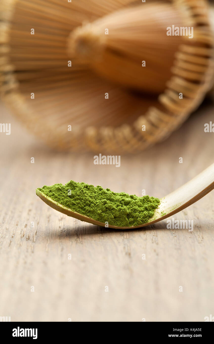 Japanese bamboo matcha spoon, chashaku, with green tea and chasen on the background - Stock Image