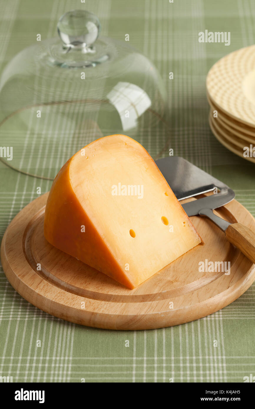 Piece of Dutch Gouda cheese on a wooden board at breakfast - Stock Image