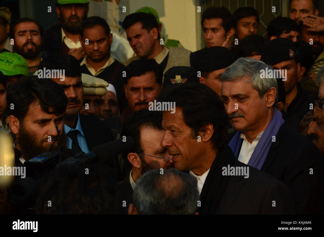 Imran Khan, leader of PTI administers polio drops to a child in Islamabad Pakistan along with KPK Chief Minister Pervez Khattak and Jahangir Tareen. - Stock Image