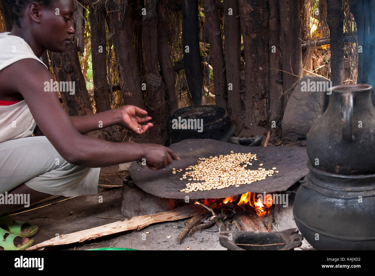 A woman roasts coffee beans on an open fire, Ethiopia, Africa - Stock Image