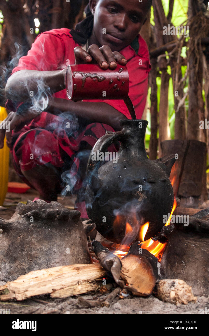 A woman pours into a traditional Ethiopian coffee pot on an open fire, Ethiopia, Africa - Stock Image