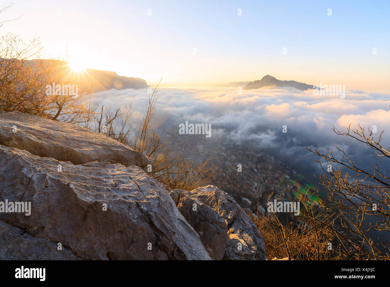Sun and mist above the city of Lecco seen from Monte San Martino, Province of Lecco, Lombardy, Italy, Europe - Stock Image