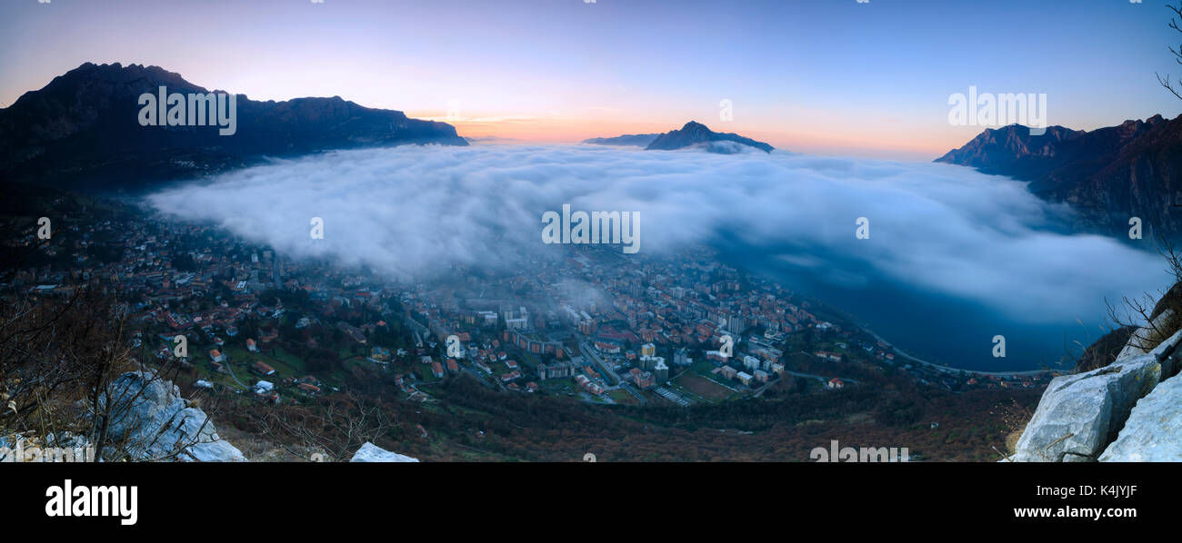 Panoramic of fog at sunrise above the city of Lecco seen from Monte San Martino, Province of Lecco, Lombardy, Italy, Europe - Stock Image
