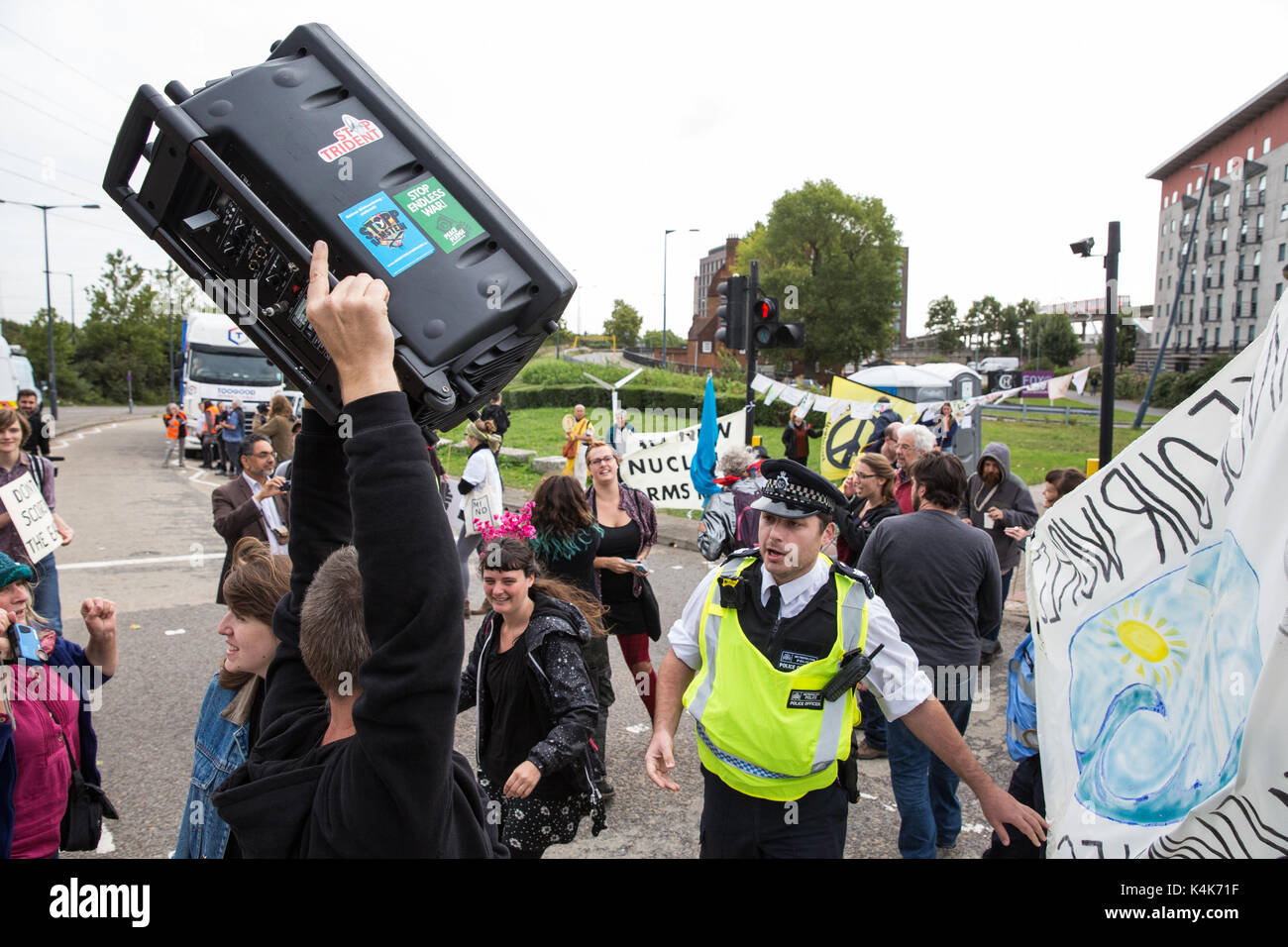 London, UK. 6th Sep, 2017. Arms to Renewables activists dance in the roadway to block the access road to the ExCel Centre to prevent military equipment arriving by truck for the DSEI arms fair next week. Credit: Mark Kerrison/Alamy Live News - Stock Image