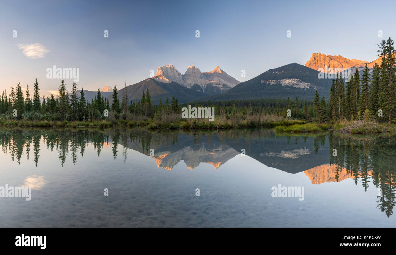 Three Sisters reflecting in calm water, morning atmosphere, Bow River, Canmore, Banff National Park, Alberta, Canada - Stock Image