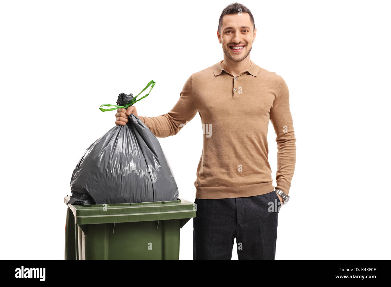 Young man throwing out the garbage and smiling isolated on white background - Stock Image