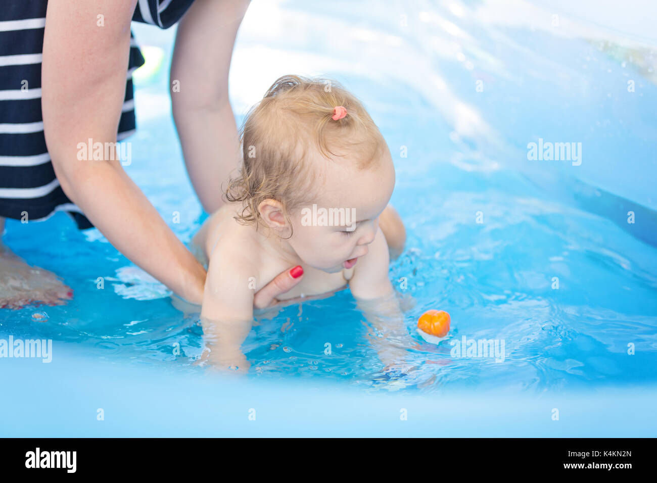 Sixteen months old baby girl playing in the plastic pool with toys - mother standing next to her, keeping an eye Stock Photo