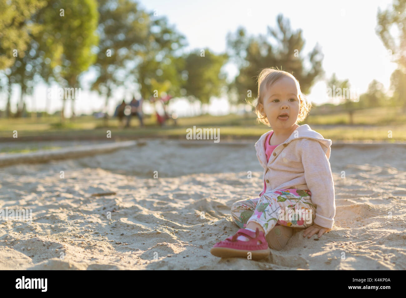 Fifteen months old baby girl playing in the sandbox in the sunset - Stock Image