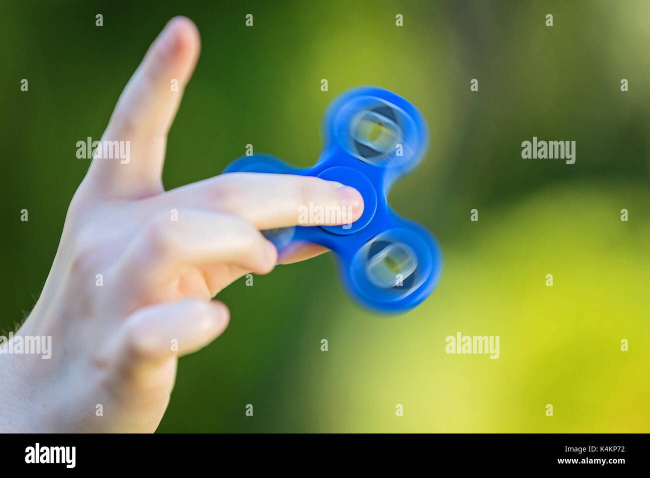 Girl's hand holding a spinning fidget spinner in her hand, spinning them on her index finger - Stock Image
