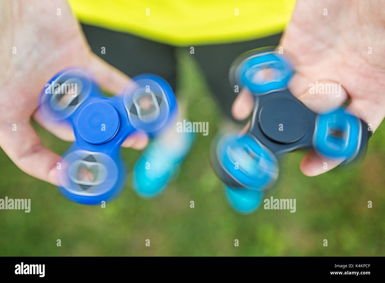 Girl holding blue and black fidget spinners in her hands, view from above; both gadgets spinning - Stock Image