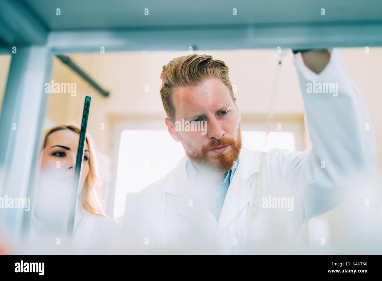 Young students of chemistry working in laboratory - Stock Image