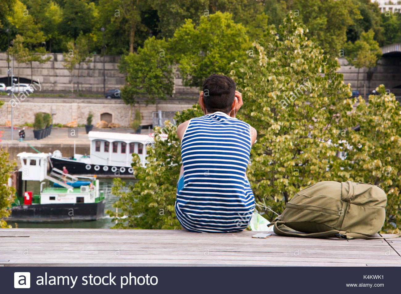 Paris (France), August 16, 2017. Young man with a marine t-shirt watching the boats on the Seine, in Paris. - Stock Image