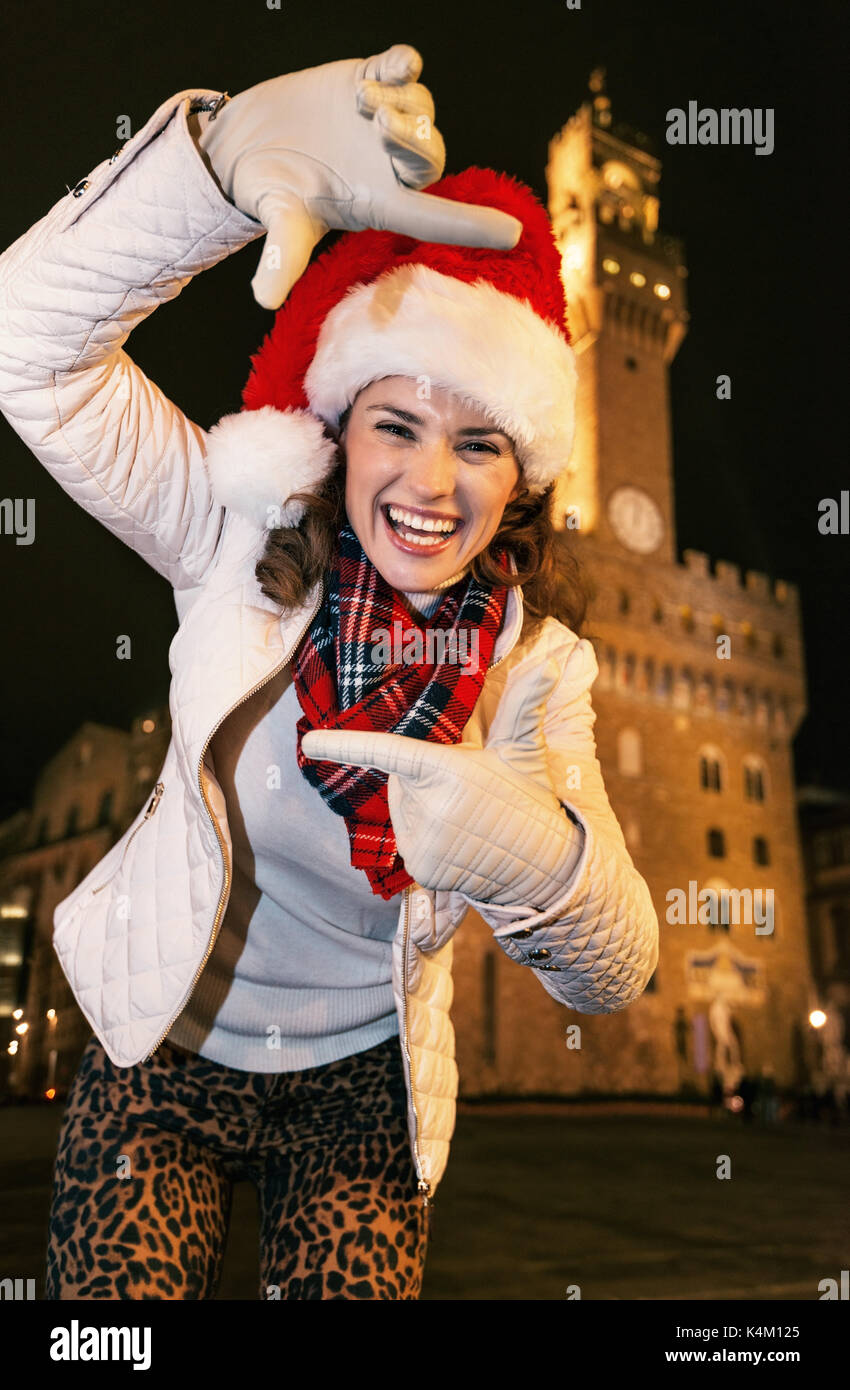Trip full of inspiration at Christmas time in Florence. Portrait of happy modern woman in Christmas hat against Palazzo Vecchio in Florence, Italy fra - Stock Image