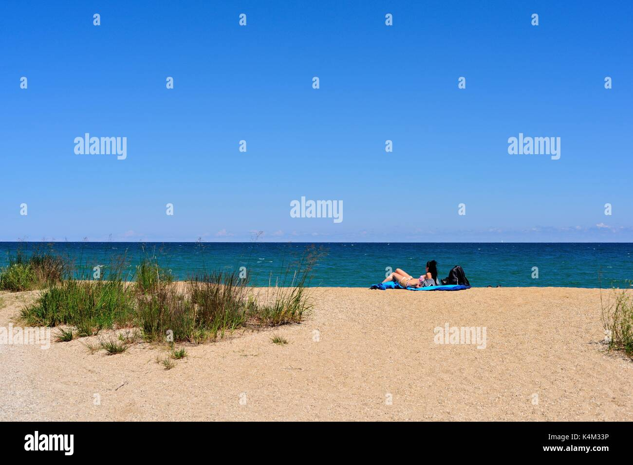A lone woman relaxes in the sand among the dunes at Illinois Beach State Park at Zion, Illinois on the shore of Lake Michigan. USA. - Stock Image