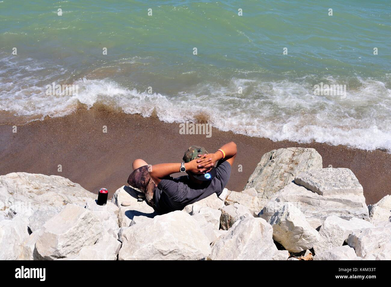 Zion, Illinois, USA. A lone man sitting among the rocks well above a beach at Illinois Beach State Park. - Stock Image